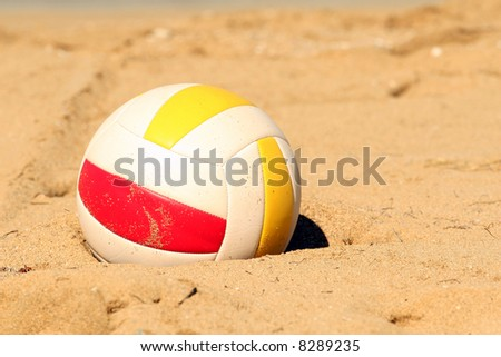 Beach volleyball lying in sand
