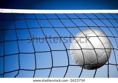 beach volleyball net in front of a beautiul blue sky by the beach - stock photo