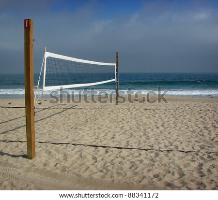 beach volleyball net with ocean in background