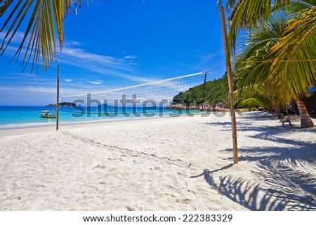 Beach volleyball on sandy beach with blue sky - stock photo