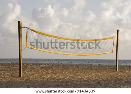 Beach volleyball  playing court with yellow net  and palm trees during early morning hours of golden light in Miami Florida with Atlantic Ocean and colorful clouds in the background. Copy Space. - stock photo