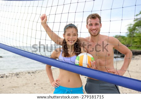 Beach volleyball portrait of people, woman and man looking at camera smiling after playing having fun in summer. Young woman and man fitness model living healthy lifestyle doing sport on beach. - stock photo