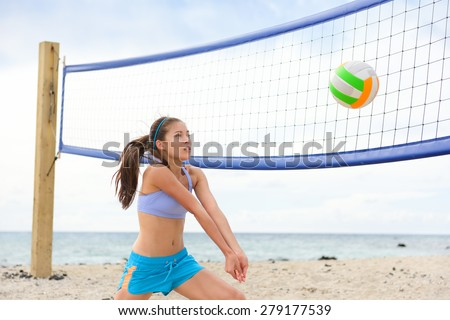 Beach volleyball woman playing game hitting forearm pass volley ball during match on summer beach. Female model living healthy active lifestyle doing sport on beach. - stock photo