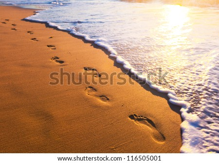 beach, wave and footsteps at sunset time - stock photo