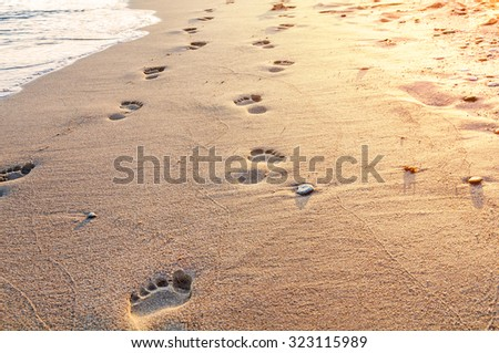 Beach, wave and footsteps in Greece, yellow light - stock photo