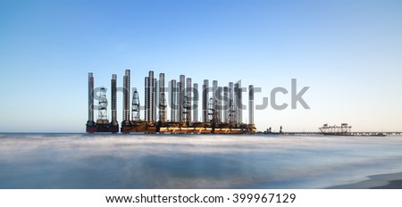 beach waves with oil platform in ocean. Caspian sea offshore oil rig drilling platform off the Baku, Azerbaijan. - stock photo