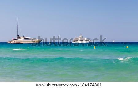 Beach, waves, yachts in bay of Saint Tropez - stock photo