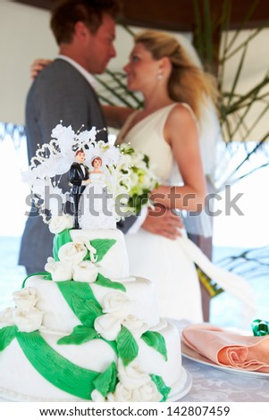 Beach Wedding Ceremony With Cake In Foreground - stock photo