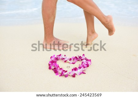 Beach wedding just married couple kissing with feet in background and rings in focus in heart shape lei flower necklace. Hawaiian marriage love concept. - stock photo