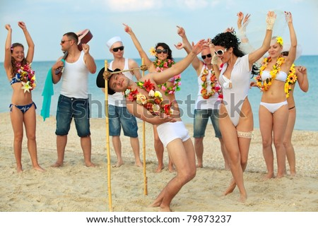 Beach wedding of happy newlywed couple have fun doing the limbo - stock photo