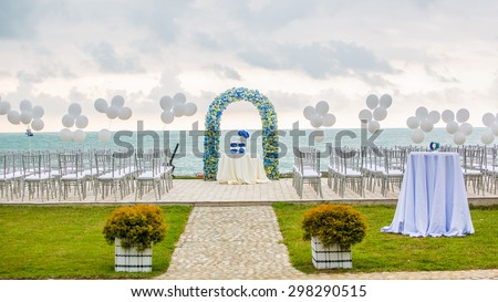 beach wedding set up, outdoor wedding reception, wedding arch - stock photo