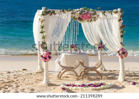 beach wedding set up, tropical outdoor wedding reception, beautiful cabana, wedding arch - stock photo