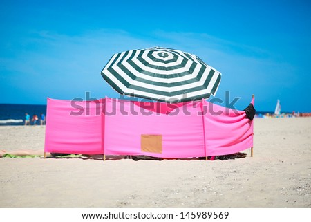 Beach wind shelter and parasol on the beach - stock photo
