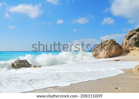 Beach with big rocks and wild sea waves - stock photo