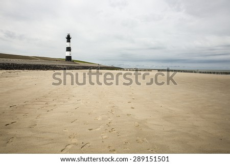 beach with black and white striped lighthouse , Nieuwe Sluis Breskens, The Netherlands - stock photo