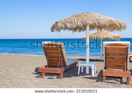 beach with black volcanic sand on Santorini island in Greece - stock photo