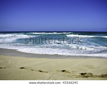 Beach with blue waters and foot print in the sand. - stock photo