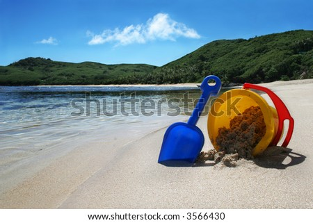 beach with clear blue water on tropical island with childrens toy bucket and spade, concept holiday - stock photo