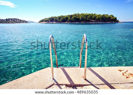 beach with clear sea water and island on horizon in Tribunj, Croatia