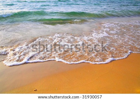 Beach with clear water and waves - stock photo