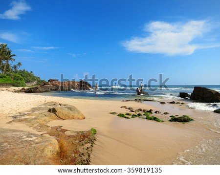 Beach with fishermen at sticks and rocks in Weligama bay, Sri Lanka - stock photo