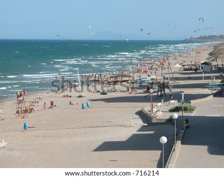 Beach with kite surfers on a sunny day (Valencia, Spain) - stock photo