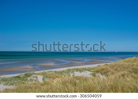 Beach with low tide water in the summer - stock photo