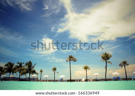 Beach with palm trees and sun loungers on the background of blue sky