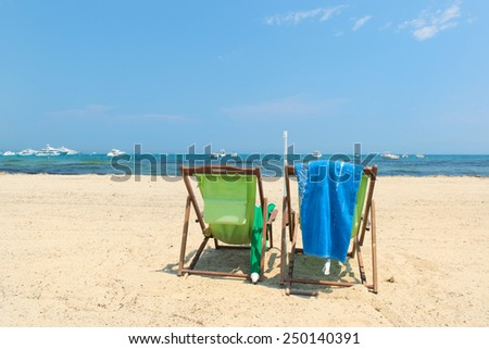 Beach with parasols, beds and luxury yachts - stock photo