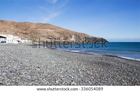 Beach with pebbles in the small fishing village of Giniginamar on the south east coast of Fuerteventura, Canary Islands, Spain.