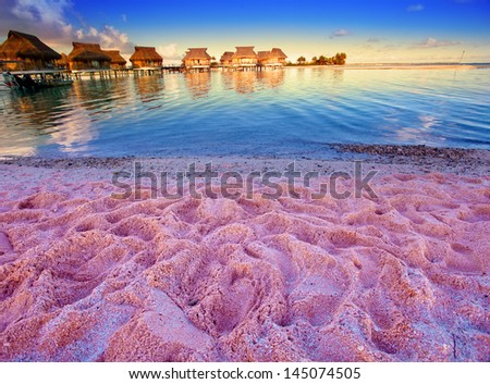 Beach with pink sand and lodges on water - stock photo