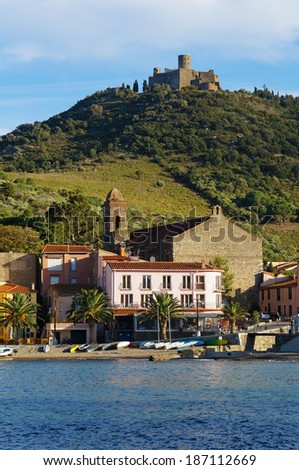 Beach with small boats in the village of Collioure and fort Saint-Elme upon the hill, Mediterranean sea, Roussillon, Pyrenees Orientales, France - stock photo