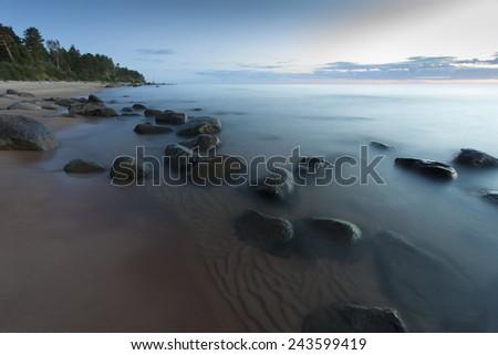 Beach with stones at sunset. Latvia - stock photo