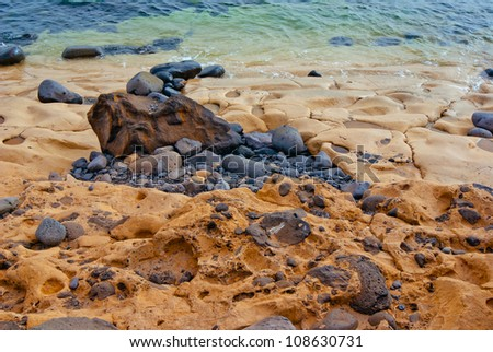 beach with stones, lava and unusual hardened sand in sunset light - stock photo