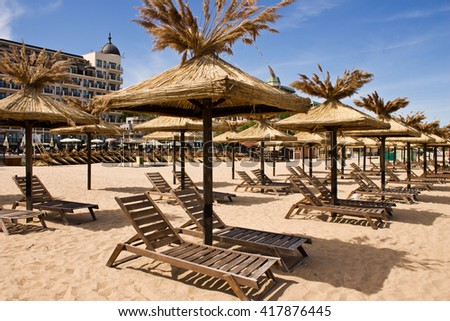 Beach with straw umbrellas and sunbeds on the background of blue sky and sea