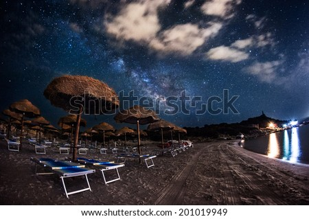 Beach with straw umbrellas at night under the stars and the Milky Way - stock photo