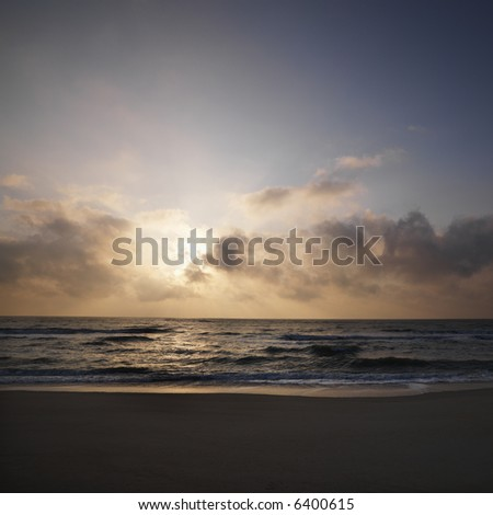 Beach with sun setting in clouds over ocean at Bald Head Island, North Carolina - stock photo
