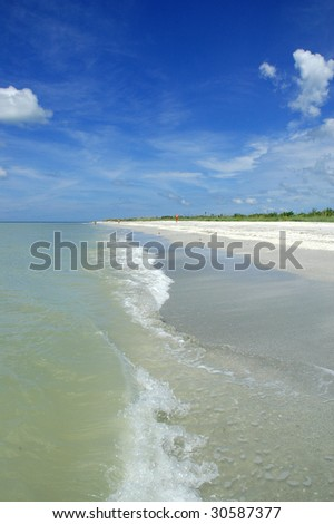 beach with surf and blue sky - stock photo