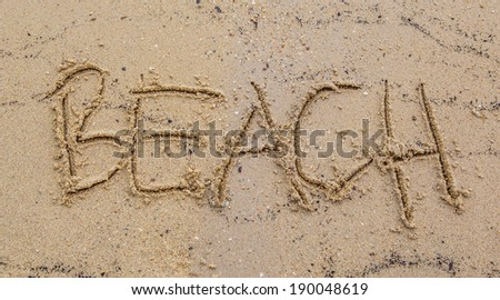 Beach with the word BEACH scribbled on the sand