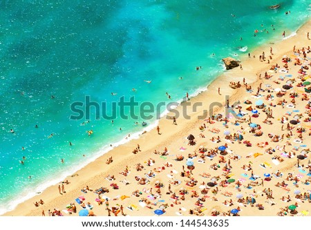 beach with tourists, sunbeds and umbrellas. sea travel destination. holidays background. top view - stock photo