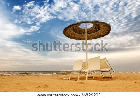 beach with umbrellas and sunbeds in rimini,italy in summer - stock photo