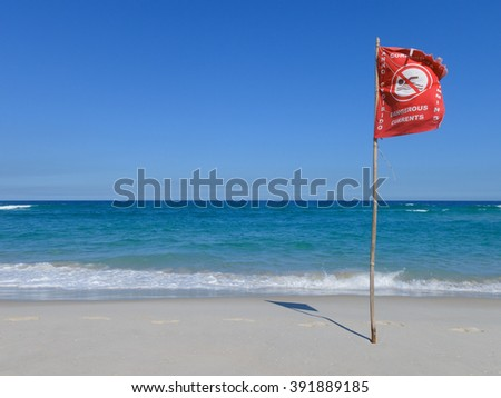 Beach with warning flag because of dangerous currents in Rio de Janeiro, Brazil. - stock photo