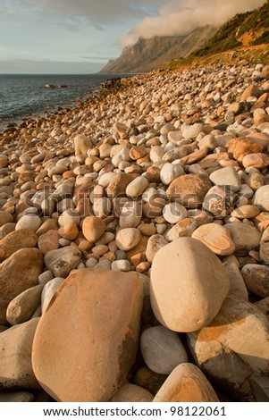 Beach with white rocks in the late afternoon sun. - stock photo