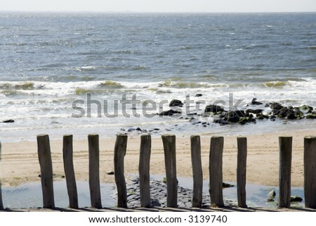 Beach with wooden poles on the foreground - stock photo