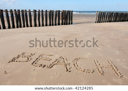 Beach with wooden wave breakers in landscape and text - stock photo