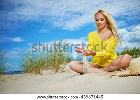 Beach woman funky happy and colorful wearing beach hat having summer fun during travel holidays vacation. trendy cool hipster woman in bikini lying in the sand. - stock photo