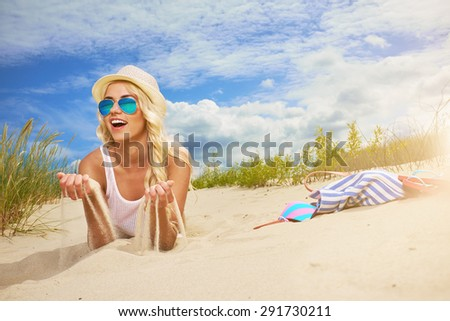 Beach woman funky happy and colorful wearing sunglasses and beach hat having summer fun during travel holidays vacation. - stock photo