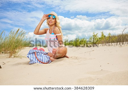 Beach woman funky happy and colorful wearing sunglasses and beach hat having summer fun during travel holidays vacation.