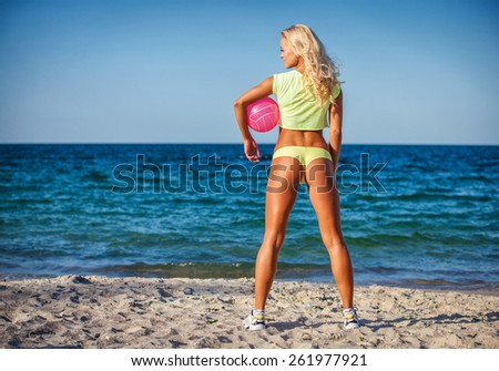 Beach woman in bikini holding a volleyball - stock photo