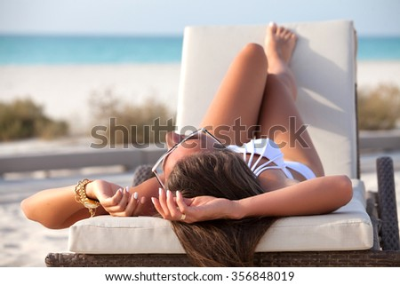 Beach woman in white bikini enjoying the summer sun, happy laying in a sunbed at the tropical beach with face raised to the sunlight. - stock photo